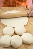 Woman rolling out tortilla dough