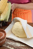 Tortilla dough and cobs of corn, woman in background