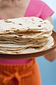 Woman holding freshly baked tortillas on tray