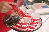 Woman pouring coffee into a paper cup (4th of July, USA)