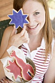 Woman holding a star cookie in front of her eye (4th of July, USA)