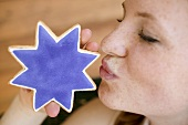 Woman kissing star-shaped cookie (4th of July, USA)