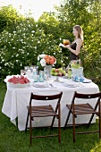 Woman bringing drink to table laid in garden