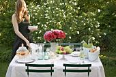 Frau stellt Teller auf gedeckten Tisch im Freien