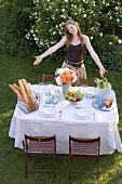Woman presenting table laid in garden