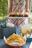 Chips and iced tea on table, woman serving hamburgers