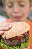 Small boy holding hamburger
