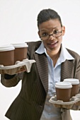 Businesswoman holding four cups of coffee