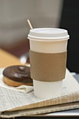 Coffee in paper cup and doughnut on newspaper in office