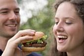 Man offering woman a bite of hamburger