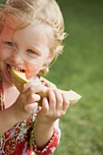 Small girl eating a slice of melon