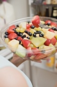 Woman eating fruit salad out of large plastic bowl