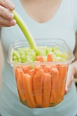 Woman eating celery out of plastic container