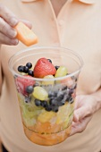 Woman taking piece of melon out of plastic tub of fruit salad