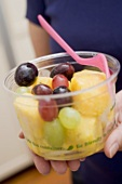 Woman holding plastic tub of fruit salad with fork