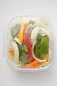 Sliced vegetables in plastic container (overhead view)