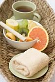 Cup of tea, fresh fruit and towel in basket