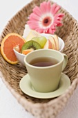 Cup of tea, fresh fruit, towel and flower in basket