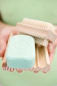 Frau hält Seife, Seifenschale und Bürste