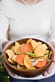 Woman holding wooden bowl of vegetable crisps