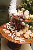 Hand reaching for Christmas biscuit on tiered stand