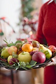 Woman holding bowl of fruit (Christmas)
