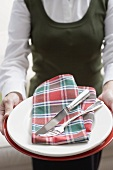 Woman holding tableware for a Christmas place setting