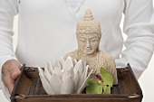 Woman holding Buddha statue, candle and orchid on tray