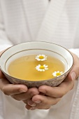 Hands holding bowl of chamomile tea with flowers