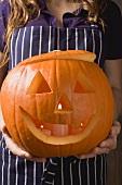 Woman holding pumpkin lantern for Halloween