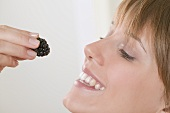 Woman holding a blackberry up to her mouth