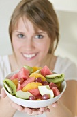 Woman holding dish of fruit salad