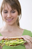 Woman holding healthy avocado and sprout sandwich