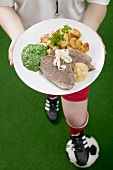 Footballer holding plate of boiled beef with accompaniments