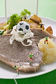 Boiled beef with accompaniments and football figures