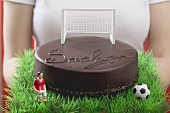 Woman holding Sacher torte with football figure & football