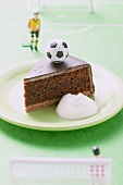 Piece of Sacher torte with cream, football & football figure