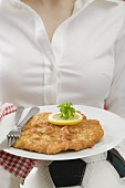Woman holding plate of Wiener schnitzel (veal escalope) on football
