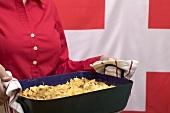 Woman serving cheese and onion pasta bake (Switzerland)