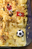 Cheese & onion pasta bake, football figure, football, flag (detail)