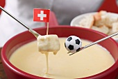 Woman eating cheese fondue, toy football on fondue fork