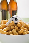 Peanut puffs with whistle in bowl in front of bottles of beer