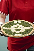 Female footballer holding spinach and mozzarella pizza
