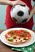 Tomato & mozzarella pizza, female footballer in background