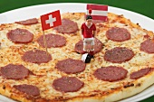 Salami pizza with toy footballer and two flags