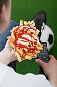 Football fan holding chips and remote