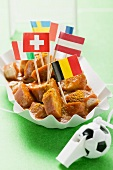 Currywurst with various flags in paper dish
