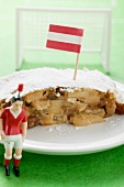 Piece of apple strudel with Austrian flag on plate