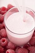 Raspberry shake in glass, surrounded by fresh raspberries