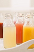 Various different juices in small bottles on tray